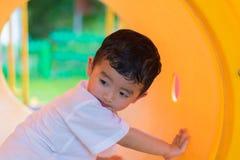 Śliczna Azjatycka chłopiec bawić się i ono uśmiecha się w żółtym tunelu przy playg Fotografia Royalty Free
