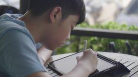 Śliczna azjatykcia chłopiec używa pastylka komputer, młody nastoletni chłopak robi pracie domowej na cyfrowej pastylce z twarzą p zdjęcie wideo