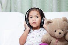 Śliczna azjatykcia dziecko dziewczyna ma zabawę słuchać muzykę Zdjęcia Stock