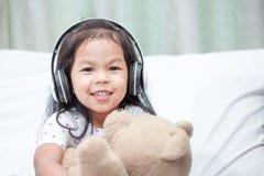 Śliczna azjatykcia dziecko dziewczyna ma zabawę słuchać muzykę Zdjęcia Royalty Free