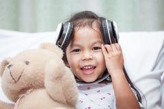 Śliczna azjatykcia dziecko dziewczyna ma zabawę słuchać muzykę Zdjęcie Stock