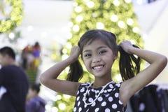 Śliczna azjatykcia dziewczyna cieszy się z bożonarodzeniowe światła Zdjęcia Stock