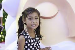 Śliczna azjatykcia dziewczyna w czerni sukni z białym punktu i krawata włosy cieszy się z dużą lalą Zdjęcie Stock