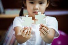 Śliczna azjatykcia mała dziewczynka próbuje łączyć pary wyrzynarki łamigłówkę Fotografia Stock