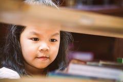 Śliczna azjatykcia mała dziewczynka znajduje książkę na półka na książki Zdjęcie Royalty Free