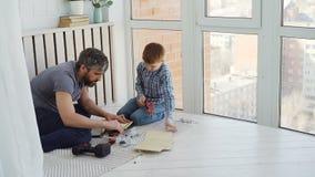 Śliczna baczna chłopiec robi woodwork pracuje z młotem i cążkami podczas gdy jego doświadczony ojciec uczy on i zbiory wideo