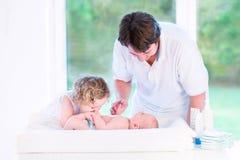 Śliczna berbeć dziewczyna całuje jej nowonarodzonego dziecko brata Zdjęcia Stock