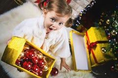 Śliczna berbeć dziewczyna dekoruje choinki czerwone jaja Obraz Stock
