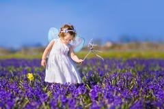 Śliczna berbeć dziewczyna w czarodziejskim kostiumu w kwiatu polu Zdjęcia Royalty Free