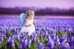 Śliczna berbeć dziewczyna w czarodziejskim kostiumu w kwiatu polu