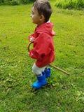 Śliczna berbeć pozycja na łące z błękitnymi podeszczowymi butami i czerwieni podeszczową kurtką Obrazy Royalty Free