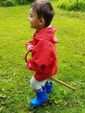 Śliczna berbeć pozycja na łące z błękitnymi podeszczowymi butami i czerwieni podeszczową kurtką Fotografia Royalty Free