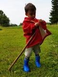 Śliczna berbeć pozycja na łące z kijem i czerwień rolników kurtką Zdjęcia Stock