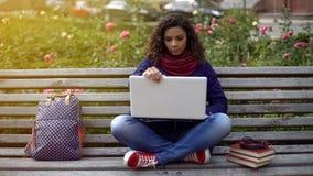 Śliczna biracial dziewczyna niósł daleko od podniecającym badawczym projektem, siedzi w parku Zdjęcia Royalty Free