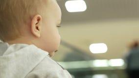 Śliczna blond chłopiec dwa roku z jego matką wspina się eskalator w wielkim centrum handlowym Dzieciak patrzeje wszystko wokoło zbiory wideo