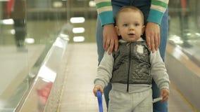 Śliczna blond chłopiec dwa roku z jego matką wspina się eskalator w wielkim centrum handlowym Dzieciak patrzeje wszystko wokoło zdjęcie wideo