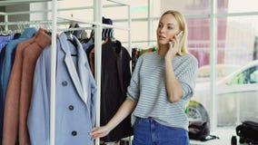 Śliczna blond dziewczyna gawędzi na mądrze telefonie w butiku, dotykający odziewa na wieszakach i ono uśmiecha się Udziały modny zbiory