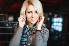 Śliczna blondynki dziewczyna jest ubranym hełmofony i ono uśmiecha się Fotografia Royalty Free