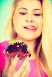 Śliczna blondynki kobieta wokoło jeść babeczkę Obraz Stock
