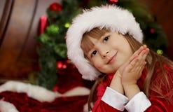 Śliczna Bożenarodzeniowa mała dziewczynka w Santa kapeluszu Zdjęcia Stock