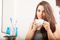 Śliczna brunetka budzi się up z niektóre kawą zdjęcia stock