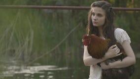 Śliczna brunetka w bielu smokingowym i jej kogucie, wiejski życie zdjęcie wideo