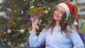 Śliczna brunetka w Santa ` s kapeluszowym przedstawieniu świąteczny prezent w złotym opakowaniu zbiory
