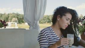 Śliczna brunetka z kędziorami relaksującymi przy lato tarasem zbiory wideo
