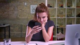 Śliczna caucasian biznesowa dziewczyna scrolling jej smartphone podczas gdy siedzieć salowy przy ekranem w biurze i patrzeć dokła