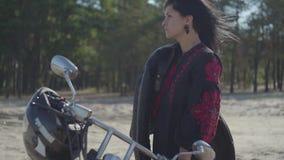 Śliczna caucasian brunetki dziewczyny pozycja przy motocyklem patrzeje daleko od przed sosnowym lasowym hobby, podróżuje i zbiory wideo