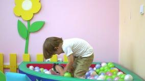 Śliczna caucasian chłopiec i dziewczynka bawić się w wielo- coloured balowym basenie preschool zbiory