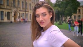 Śliczna caucasian dziewczyna jest uśmiechniętym chłodem przy kamerą i patrzeć prosto w ruchu, miasto widok, ulica, dzień