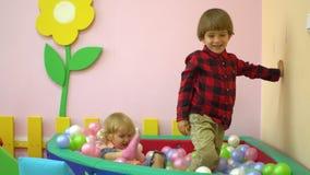 Śliczna caucasian preschool chłopiec, dziewczyna bawić się w wielo- coloured balowym basenie i Przedszkole zdjęcie wideo