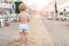 Śliczna caucasian toodler chłopiec chodzi samotnie na piaskowatej plaży między holem Uroczy szczęśliwy dziecko ma zabawę bawić si zdjęcia stock