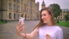 Śliczna caucasian ufna kobieta ma rozmowę telefoniczną z kamerą, opowiada emocjonalnie i ono uśmiecha się z ulicą,