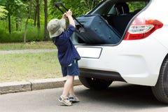 Śliczna chłopiec ładuje jego skrzynkę Fotografia Royalty Free