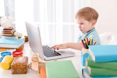 Śliczna chłopiec absorbedly używa laptop zdjęcia royalty free