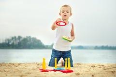 Śliczna chłopiec bawić się gemowego miotanie dzwoni na nadbrzeżu zdjęcia royalty free