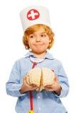 Śliczna chłopiec bawić się lekarkę z zabawkarskim ludzkim cerebrum zdjęcia stock