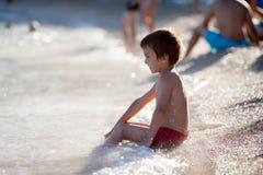 Śliczna chłopiec bawić się na plaży w wodzie Fotografia Royalty Free