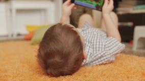 Śliczna chłopiec bawić się na telefonie, bawić się z pastylka komputerem zbiory