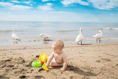 Śliczna chłopiec bawić się w piasku z plażowymi zabawkami zdjęcia stock