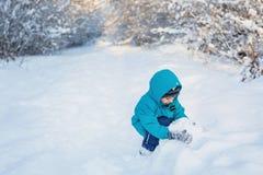 Śliczna chłopiec bawić się z śniegiem w zima lesie Obrazy Stock
