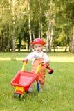 Śliczna chłopiec bawić się z czerwonym wheelbarrow w lato parku Fotografia Stock