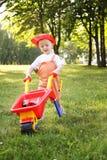 Śliczna chłopiec bawić się z czerwonym wheelbarrow w lato parku Obrazy Stock
