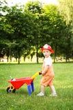 Śliczna chłopiec bawić się z czerwonym wheelbarrow w lato parku Obrazy Royalty Free