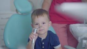 Śliczna chłopiec bawić się z medycznymi narzędziami siedzi w krześle w dentysty biurze Beztroski dziecko odwiedza lekarkę zbiory