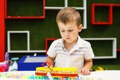 Śliczna chłopiec bawić się z tramwajem Chłopiec bawić się z samochód zabawką zdjęcie royalty free