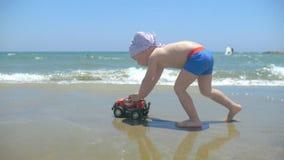 Śliczna chłopiec bawić się z zabawkarskim samochodem na plaży Dzieci pchnięć ręki zabawki ciężarówka zbiory wideo