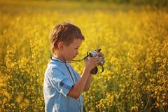 Śliczna chłopiec bierze obrazki kwiaty na koloru żółtego polu w lecie zdjęcie stock